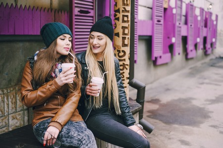 stylishly: two beautiful girls walk around town fashionably and stylishly dressed with a Cup of coffee