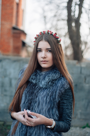 carven girl in a wreath on the street with a phone Stock Photo