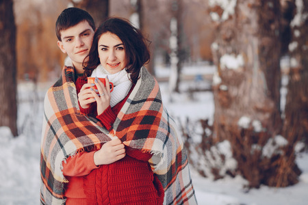 couple walking through winter streets, drinking coffee and photographed on phone