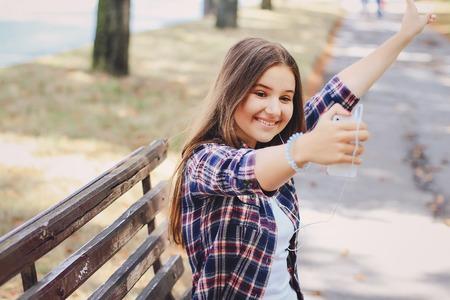 jong mooi meisje lopen park. goede tijd. maakt gebruik van de communicatiemiddelen. spelen met de hond