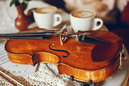 a violin is on the table and a cup of coffee next to it 写真素材
