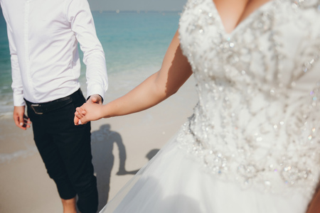 a young and beautiful bride in a white dress walks around the summer sea with her fiancée