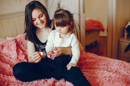 Mother with daughter sitting on a bed