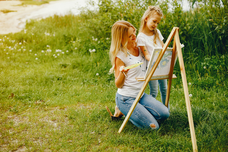 Mother with daughter drawing in a park