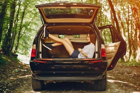 Girl in a summer park near car Stock Photo