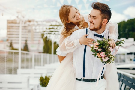 Beautiful bride with her husband in a park Stock Photo