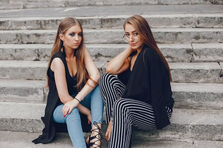 Fashion girls sitting in a summer city