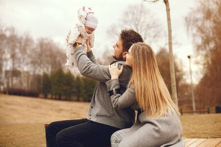 Family with daughter in a autumn park