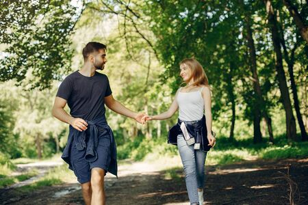 Beautiful couple spend time on a summer forest