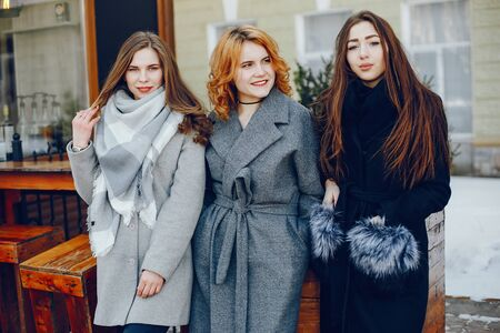 three pretty girl in a winter city