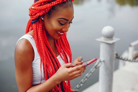 A young and stylish dark-skinned girl with red dreads sitting near river Stock Photo