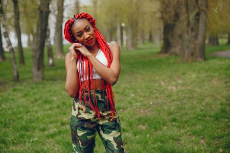 A young and stylish dark-skinned girl with red dreads walking in the summer park Stock Photo