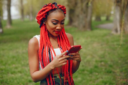 A young and stylish dark-skinned girl with red dreads walking in the summer park with phone Stock Photo
