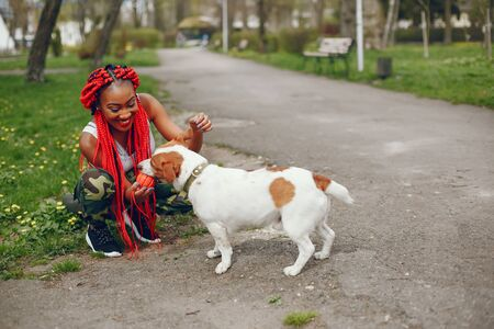 A young and stylish dark-skinned girl with red dreads walking in the summer park with dog Standard-Bild