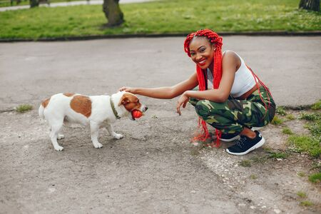 A young and stylish dark-skinned girl with red dreads walking in the summer park with dog Stock Photo
