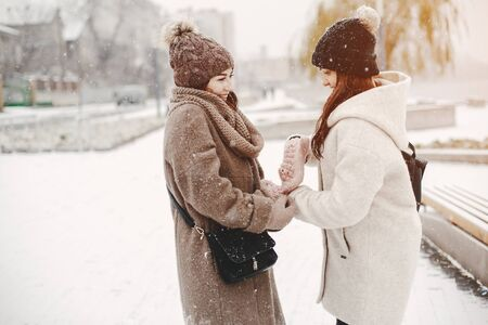 two bright and merry girls walking in the frozen snowy park