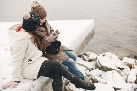 two bright and merry girls sitting in the frozen snowy park neaw water and use the phone 版權商用圖片