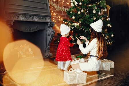 Elegant mother in a white sweater. Family with cristmas gifts. Little girl near christmas tree Stock Photo