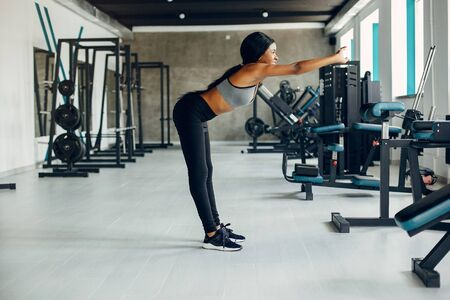 A beautiful black girl is engaged in a gym