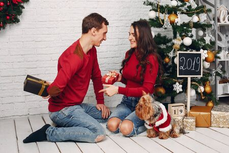Cute family at home near Christmas tree Stock Photo
