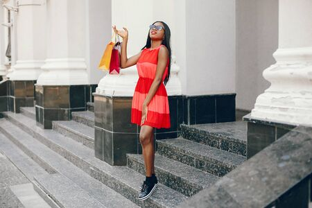 Black girl in a summer city. Woman with a shoping bags. Lady in a red ress