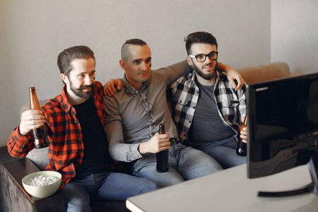 Group of fans are watching a soccer moment on the TV