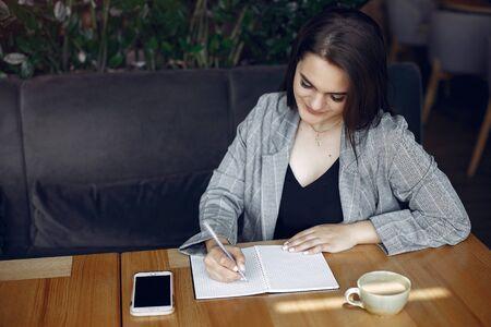 La empresaria sentada a la mesa en un café y trabajando Foto de archivo