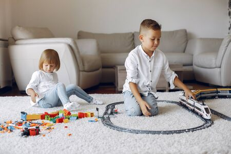 Children playing and toy train in a playing room