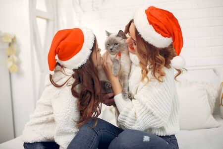 Beautiful mother in a white sweater. Family with cristmas gifts. Little girl in a santas hat Stock Photo