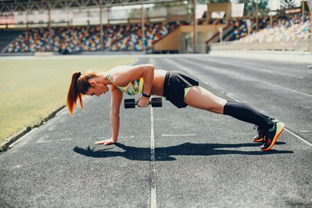 Sports girl at the stadium. Beautiful girl doing sports.The girl raises the weight Banco de Imagens