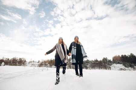 Cute girls walking in a winter park. Sisters have fun with snow. Ladies in a cute hats Reklamní fotografie - 138202547