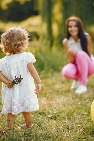 Mutter mit Tochter, die in einem Sommerpark spielt Standard-Bild