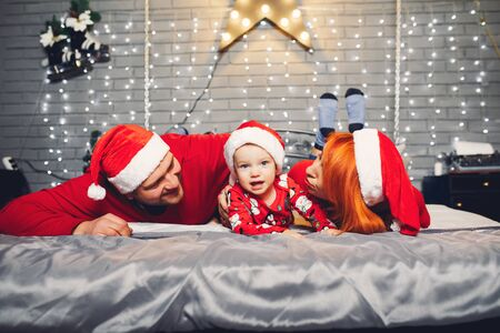 Family sitting at home on a bed in a christmas decorations Standard-Bild - 139570143