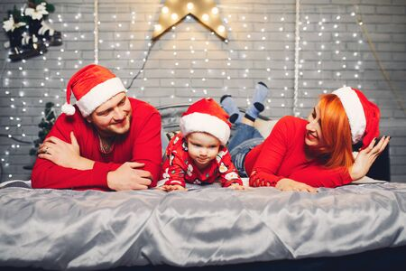 Family sitting at home on a bed in a christmas decorations Standard-Bild - 139570150