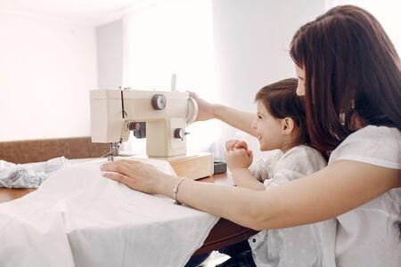 Woman sewing on a sewing machine Standard-Bild - 139570629