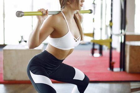 Beautiful girl in a gym. Sports girl in a sportswear. Girl training
