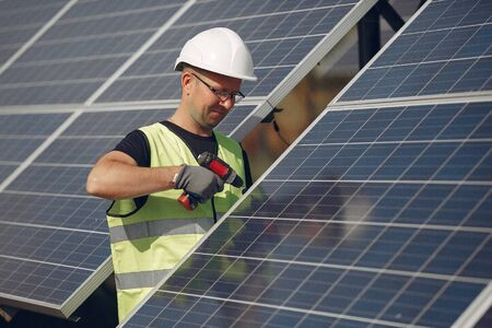 Man in a white helmet near a solar panel Banque d'images