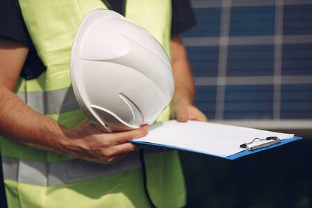 Man in a white helmet near a solar panel