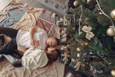 Couple near christmas tree. Lady in a white sweater. Family sitting on a floor. 版權商用圖片