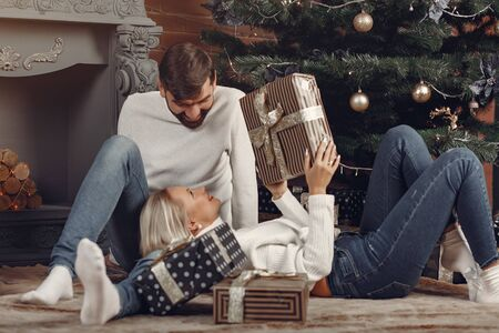 Lady in a white sweater. Family sitting on a floor. Couple near christmas tree. 版權商用圖片