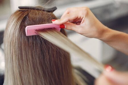 Hairdresser working with hear her client. Woman in a hair salon