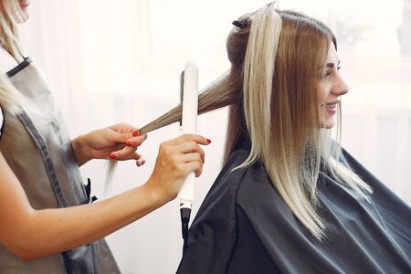 Hairdresser does hairstyle for her client