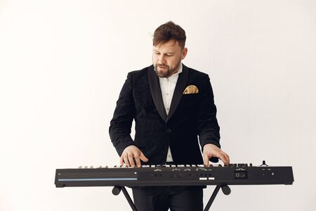 Man in black suit standing with a electro keyboard