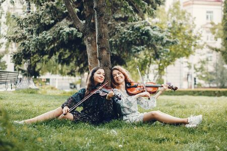 Beautiful and romantic girls in a park with a violin 写真素材