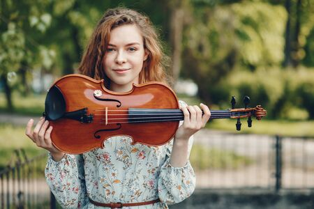 Beautiful girl in a summer park with a violin 写真素材