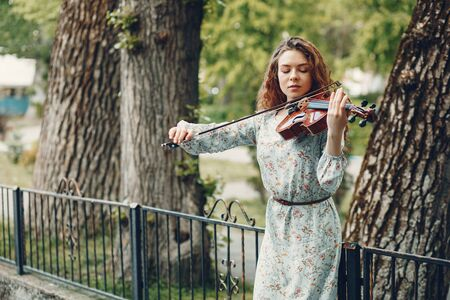 Beautiful girl in a summer park with a violin Reklamní fotografie