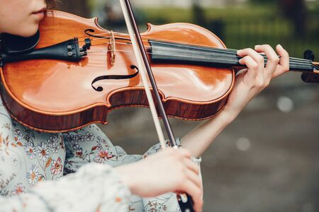 Girl in a summer park. Lady with a violin. Girl in a summer dress Zdjęcie Seryjne