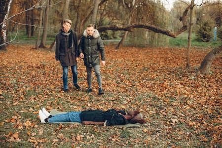 Two boys in a autumn park help a african girl Reklamní fotografie