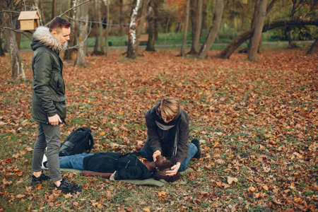 Two boys in a autumn park help a african girl