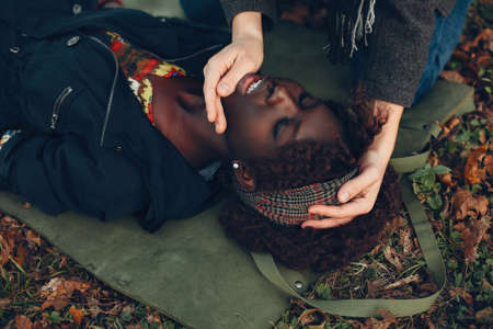 Man in a autumn park help a african girl
